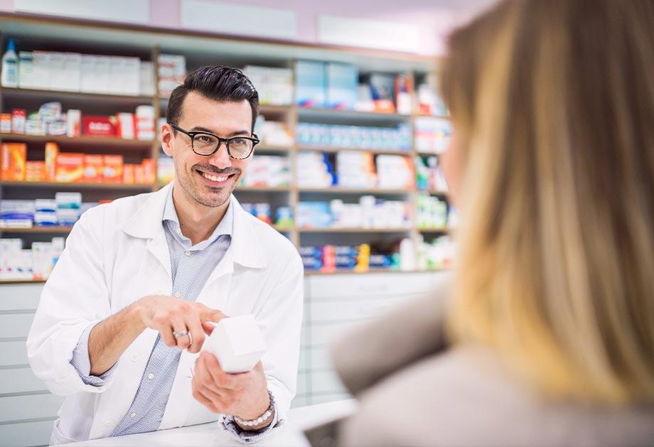 Hymyilevä farmaseutti asiakaspalvelutilanteessa